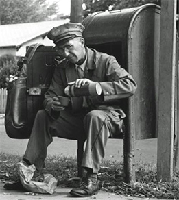 Vintage mailman sitting in post box.